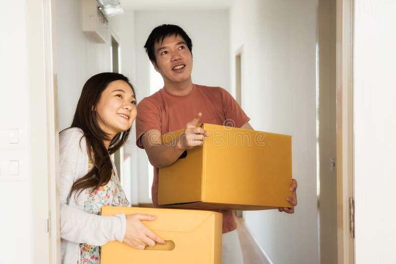 Los pares llevan las cajas al dormitorio de la nueva casa imagen de archivo