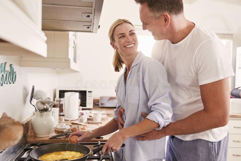 Los pares maduros cariñosos preparan el desayuno en cocina juntos imágenes de archivo libres de regalías