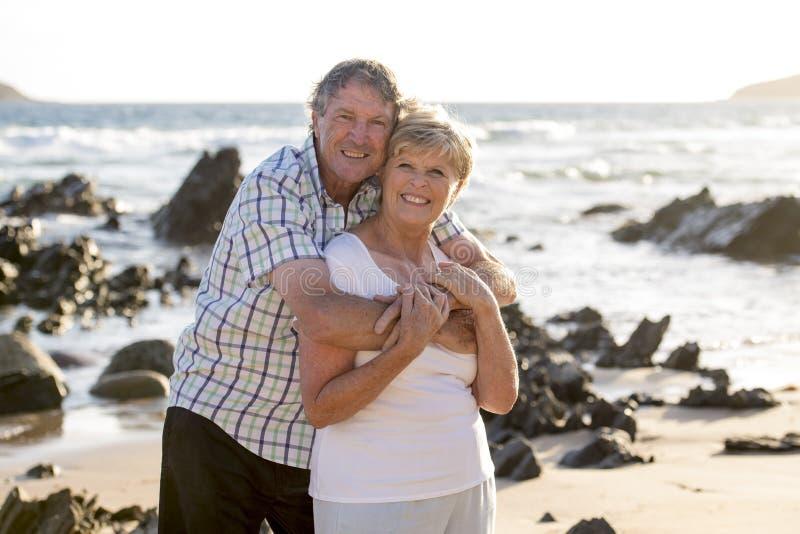 Los pares maduros mayores preciosos en su 60s o 70s retiraron caminar feliz y relajado en orilla de mar de la playa en el envejec fotos de archivo