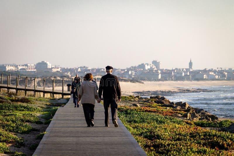 Los pares mayores caminan en paseo marítimo imagen de archivo