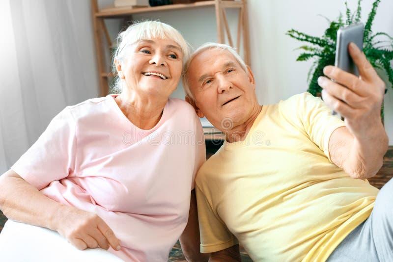 Los pares mayores ejercitan juntas en casa las fotos del selfie de la atención sanitaria felices foto de archivo