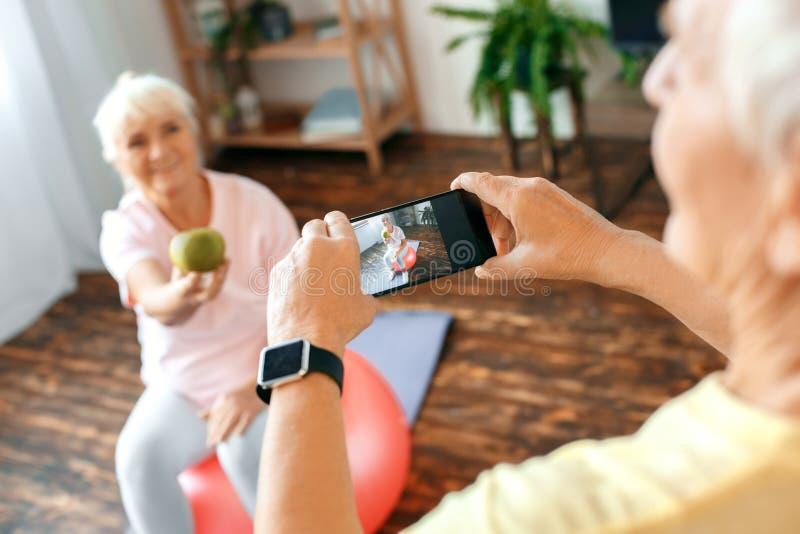 Los pares mayores ejercitan juntas en casa tomando imágenes con la manzana imagen de archivo