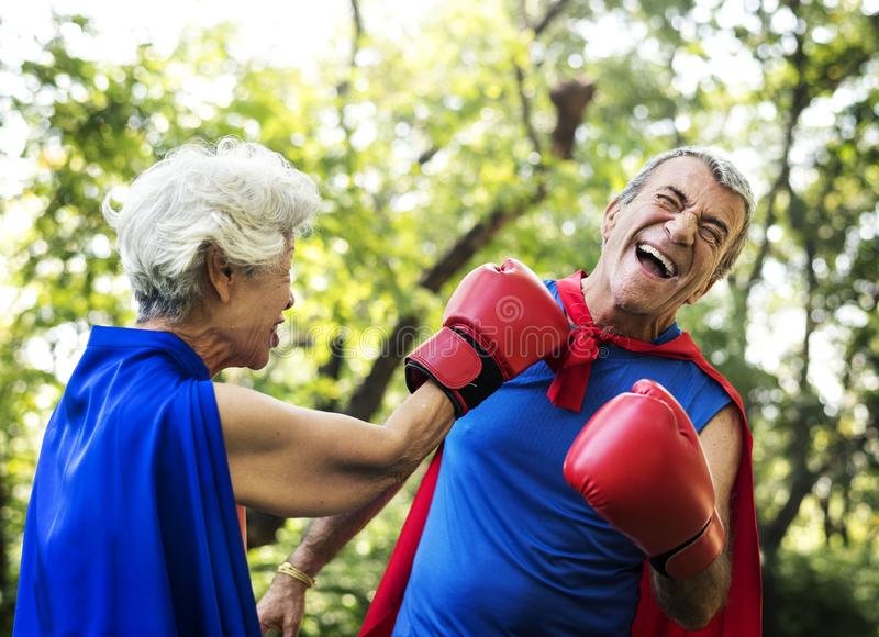 Los pares mayores en superhéroe visten listo para luchar para la diversión foto de archivo libre de regalías