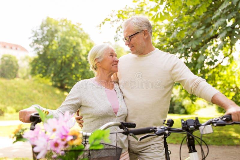 Los pares mayores felices con las bicicletas en el verano parquean imágenes de archivo libres de regalías