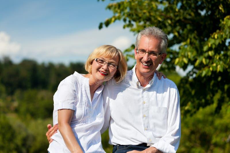 Los pares mayores felices tienen una caminata en verano imagen de archivo