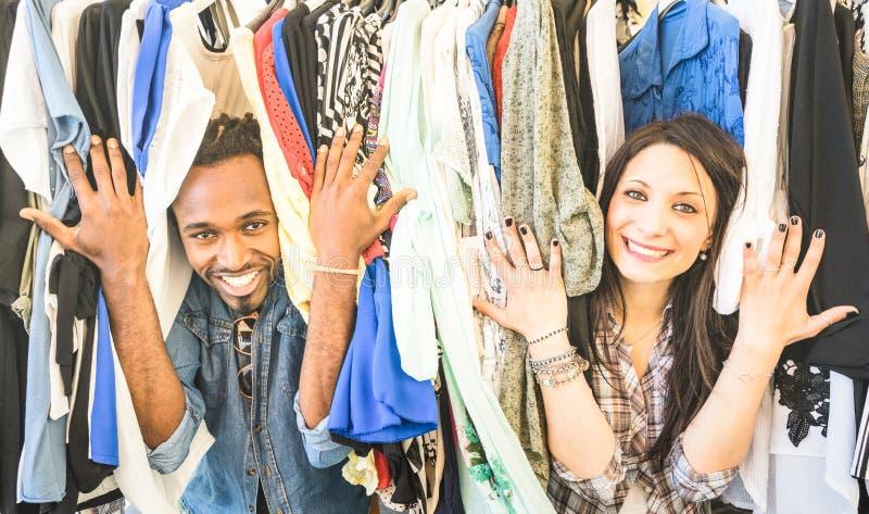 Los pares multirraciales jovenes que se divierten en el mercado de pulgas de la ropa - sea fotos de archivo