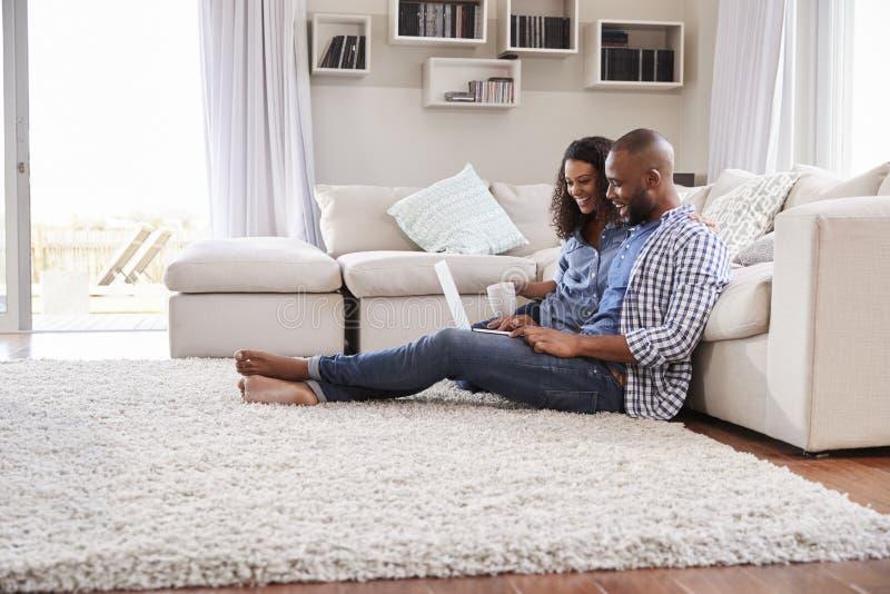 Los pares negros jovenes se sientan en el piso usando el ordenador portátil, vista lateral fotografía de archivo libre de regalías