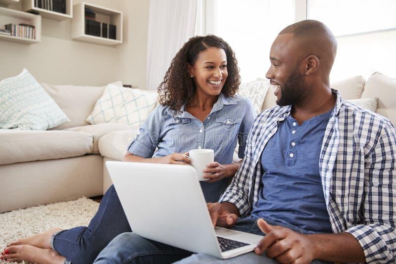 Los pares negros jovenes usando el ordenador portátil en casa miran uno a imágenes de archivo libres de regalías