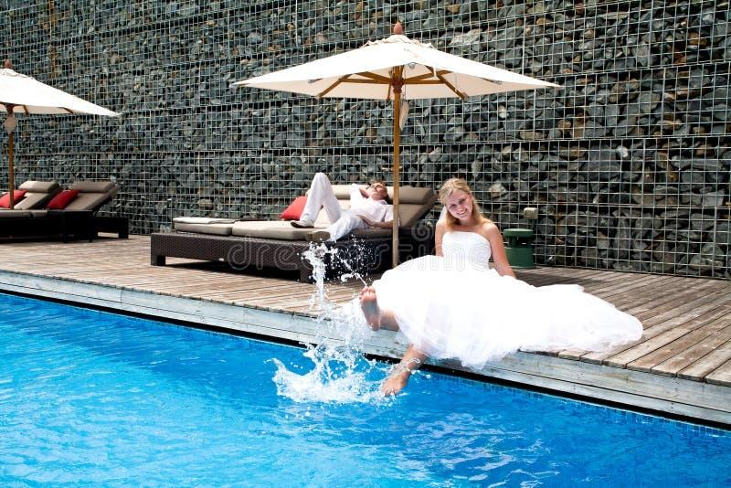 Los pares nuevamente wedding felices acercan a la piscina fotografía de archivo libre de regalías