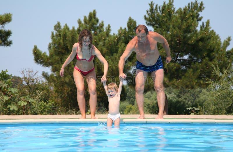 Los pares omiten al niño en piscina fotos de archivo