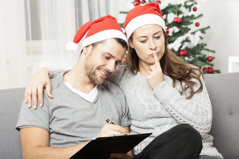 Los pares piensan alrededor para hacer la lista para la Navidad fotografía de archivo