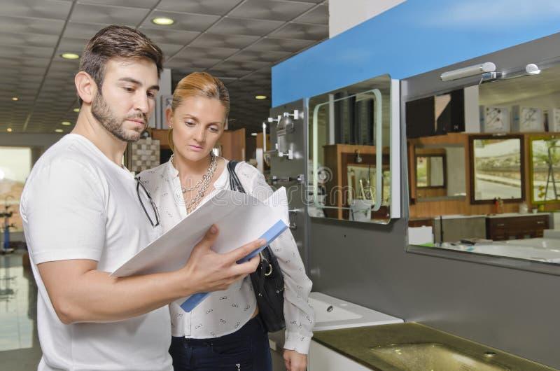 Los pares que miran el catálogo de la tienda de la fontanería y del baño reservan imagenes de archivo