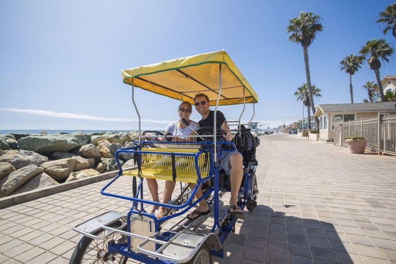 Los pares que montan una bici de Surrey montan a lo largo de la costa de California imagen de archivo