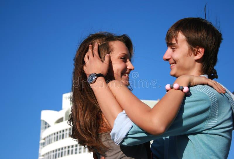Los pares que se besan felices acercan al nuevo edificio blanco fotos de archivo libres de regalías
