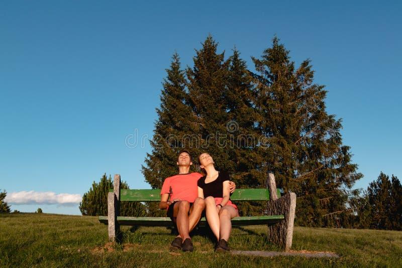 Los pares que se sientan en banco en las montañas que miran la puesta del sol y tomar broncean fotografía de archivo