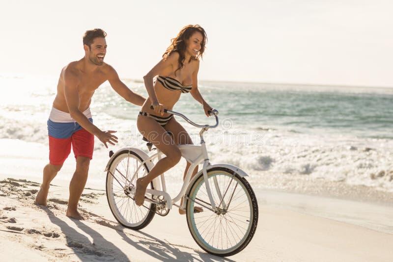 Los pares que van en una bici montan en la playa fotos de archivo
