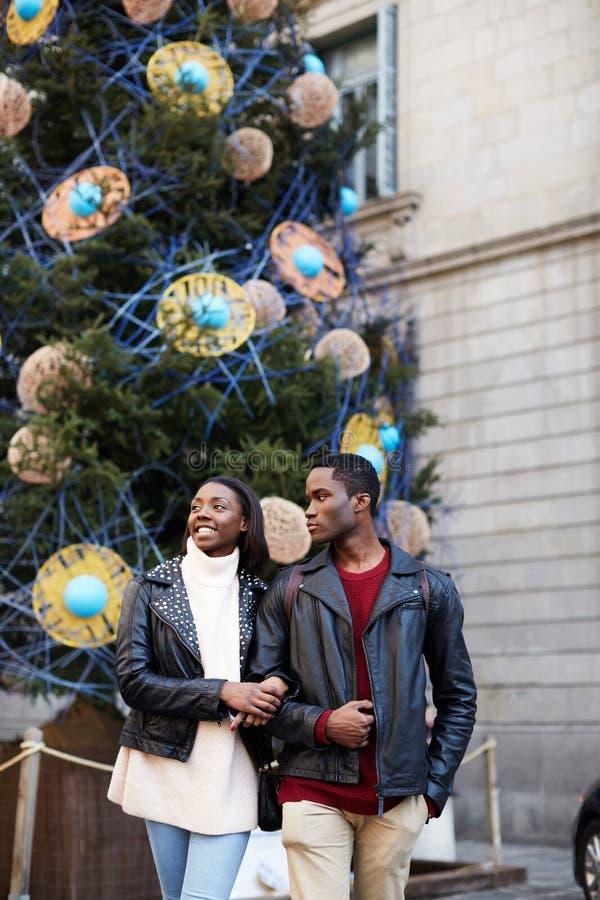 Los pares románticos caminan en fondo del árbol de navidad en cuadrado grande foto de archivo