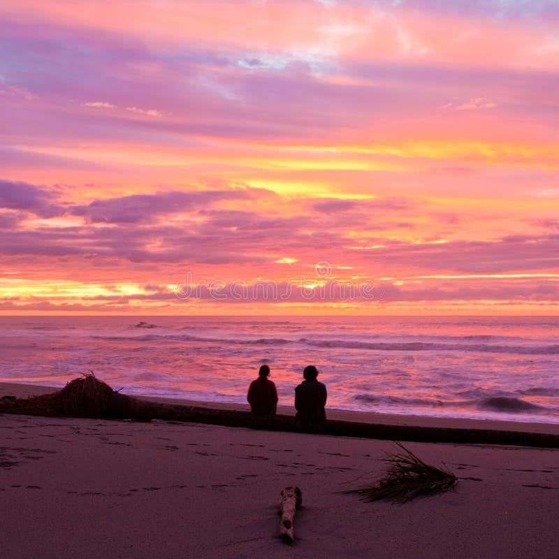 Los pares románticos disfrutan de puesta del sol espectacular de la playa fotos de archivo libres de regalías