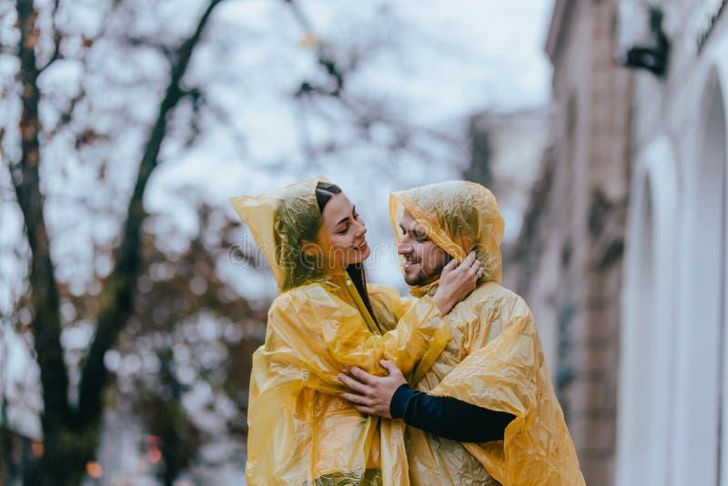 Los pares románticos, el individuo y su novia vestidos en impermeables amarillos están abrazando en la calle bajo la lluvia imagenes de archivo