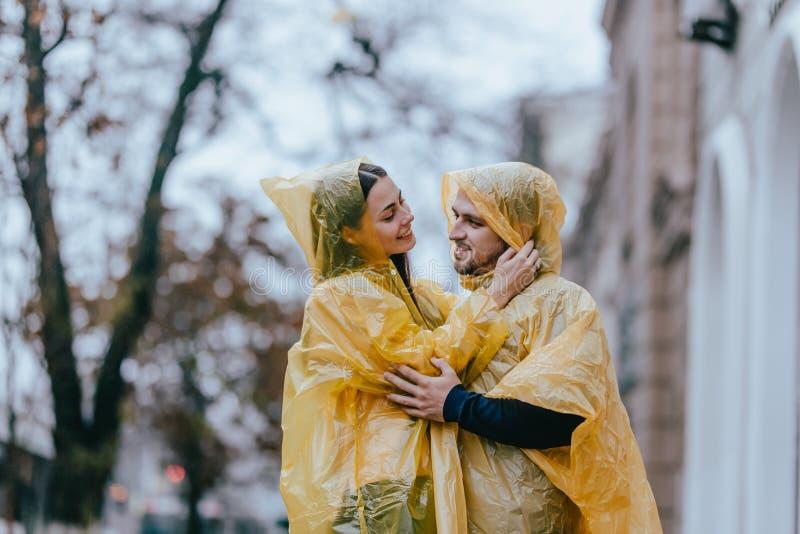 Los pares románticos, el individuo y su novia vestidos en impermeables amarillos están abrazando en la calle bajo la lluvia fotografía de archivo
