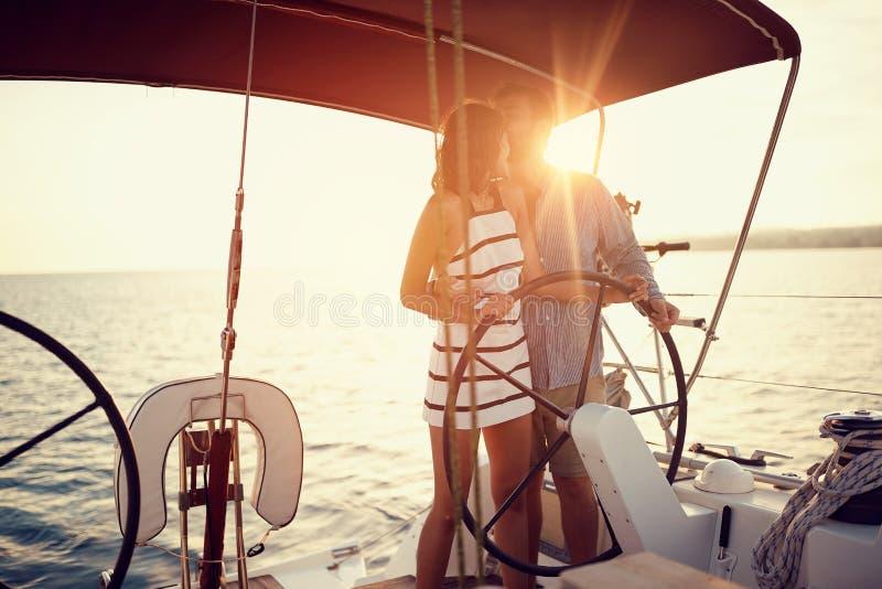 Los pares románticos en el barco de lujo juntos gozan en la puesta del sol imagenes de archivo
