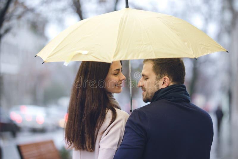 Los pares románticos felices, el individuo y su novia vestidos en ropa casual caminan debajo del paraguas y miran uno a imagenes de archivo