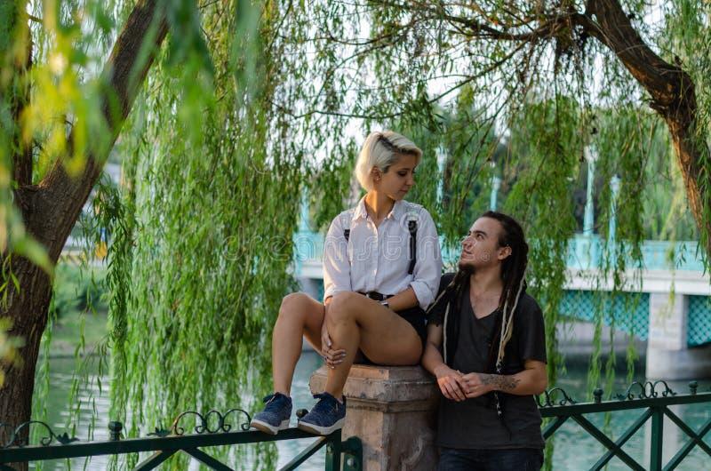 Los pares románticos felices en el parque, miran uno a imagen de archivo