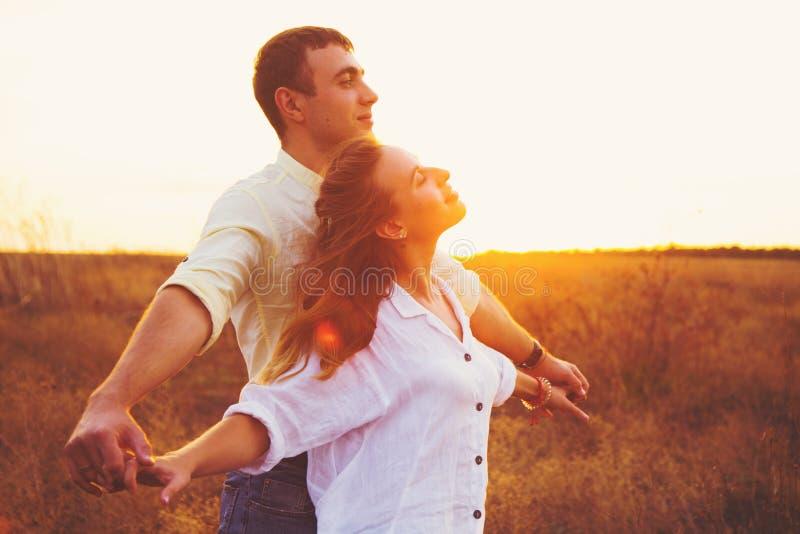 Los pares románticos jovenes que llevan a cabo las manos disfrutan de los rayos de la puesta del sol al aire libre en campo foto de archivo