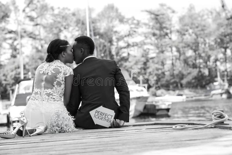 Los pares románticos que se sientan en un muelle de madera y expresan su amor fotografía de archivo libre de regalías