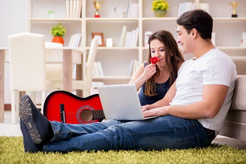 Los pares románticos que tocan la guitarra en piso imagenes de archivo