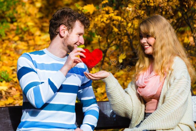 Los pares románticos se sientan en banco en parque otoñal imagen de archivo