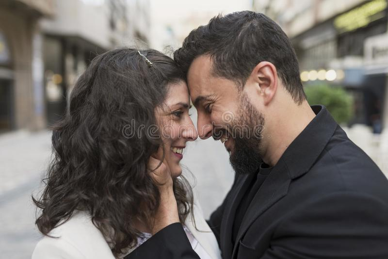 los pares 30s en la calle en amor abrazan imagen de archivo libre de regalías