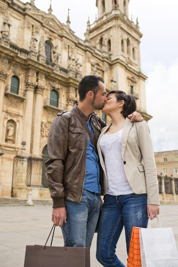 Los pares se besan cerca a la catedral con los panieres foto de archivo libre de regalías