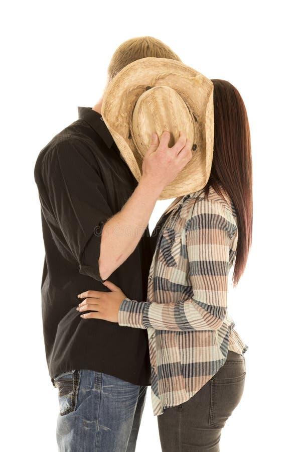 Los pares se besan detrás del sombrero foto de archivo