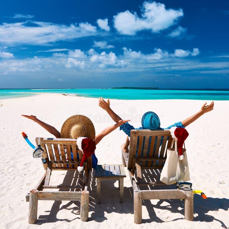 Los pares se relajan en una playa en la Navidad foto de archivo libre de regalías