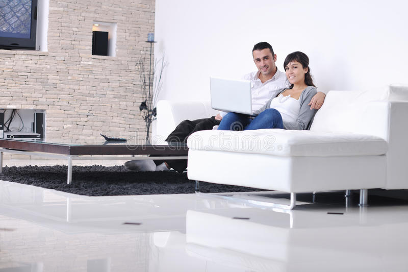 Los pares se relajan y trabajan en hogar del ordenador portátil fotografía de archivo libre de regalías