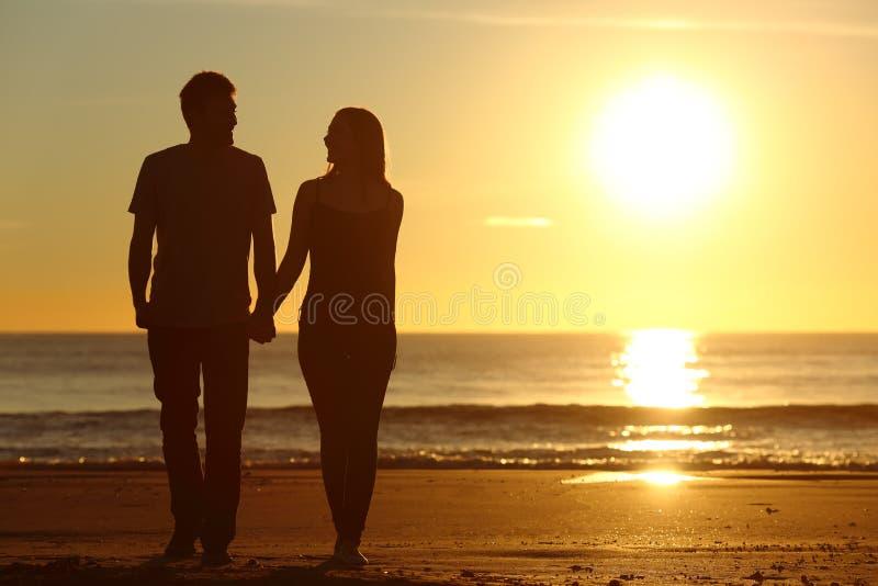 Los pares siluetean caminar juntos en la playa imagenes de archivo