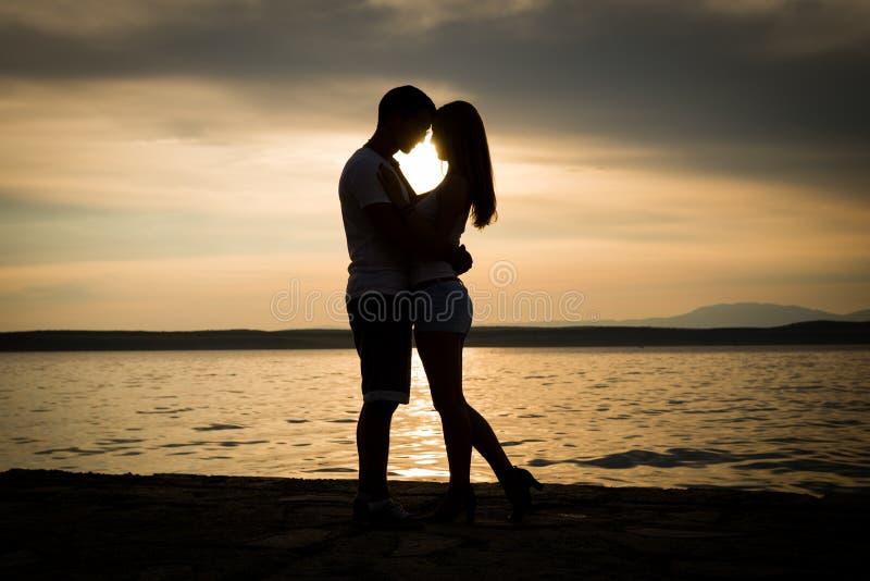 Los pares siluetean en la playa foto de archivo