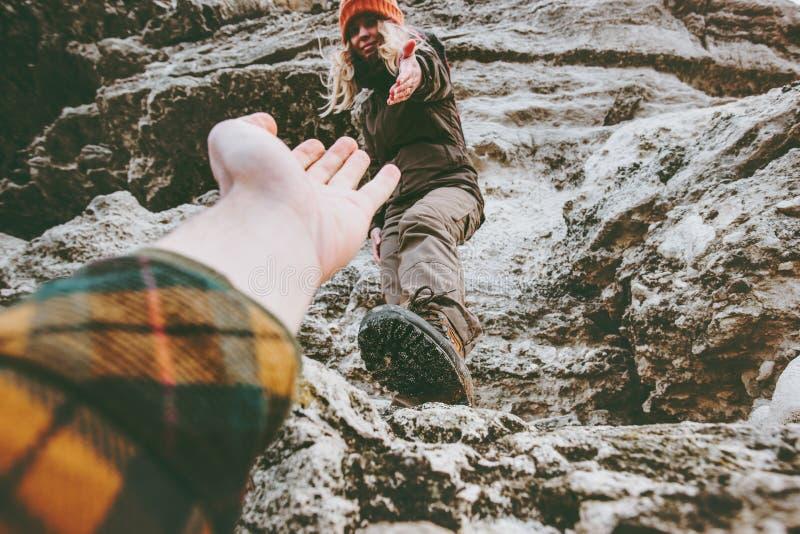 Los pares sirven y la ayuda de la mujer que da las manos que suben las montañas rocosas ama y viaja forma de vida imagenes de archivo