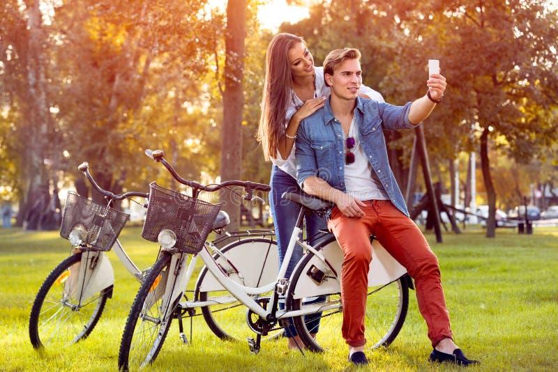 Los pares sonrientes con las bicicletas y el smartphone en otoño parquean imagen de archivo libre de regalías