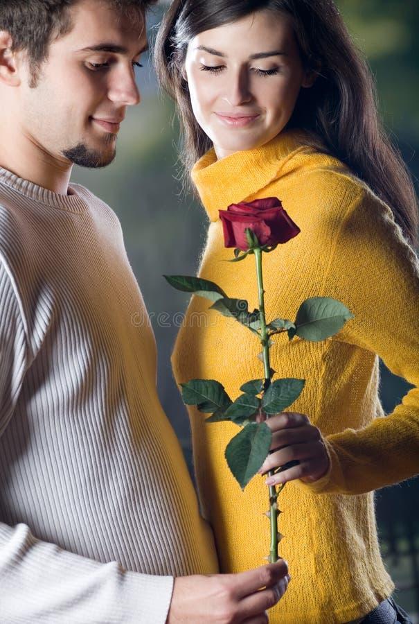 Los pares sonrientes felices jovenes con se levantaron fecha romántica imagen de archivo libre de regalías