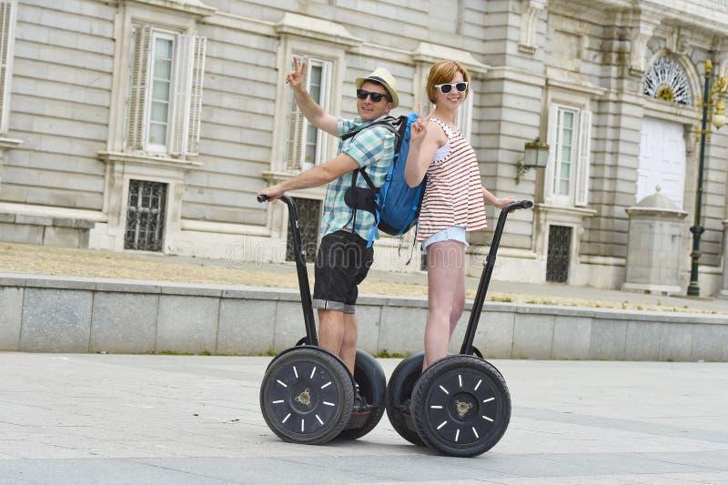 Los pares turísticos felices jovenes que montan la ciudad de goce segway viajan en el palacio de Madrid en España que se divierte imagen de archivo libre de regalías