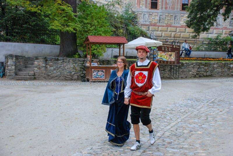 Los pares vestidos de actores caminan en la ciudad medieval de Cesky Krumlov imagenes de archivo