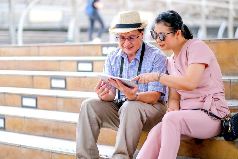Los pares viejo del turista asiático del hombre y de la mujer están mirando la tableta durante viajar de la ciudad grande Esta fo fotografía de archivo libre de regalías