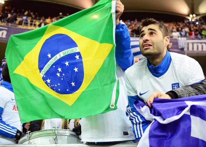 Los partidarios griegos felices celebran la calificación al mundial de la FIFA el Brasil 2014 imagen de archivo