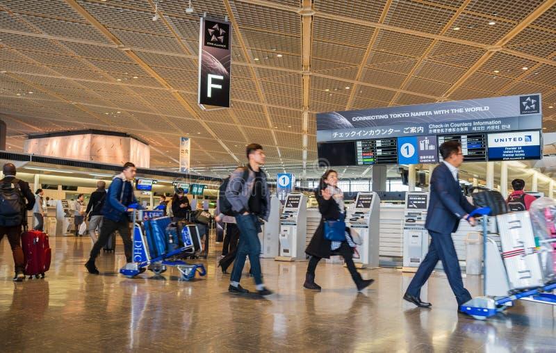 Los pasajeros dan une vuelta en el ?rea de la salida del terminal 1 en el aeropuerto internacional de Narita, Tokio, Jap?n foto de archivo