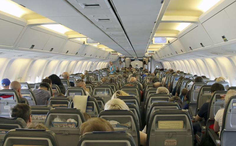 Los pasajeros de la clase de economía toman sus asientos y consiguen listos para el despegue en la cabina de Boeing 767 - el aero imagen de archivo