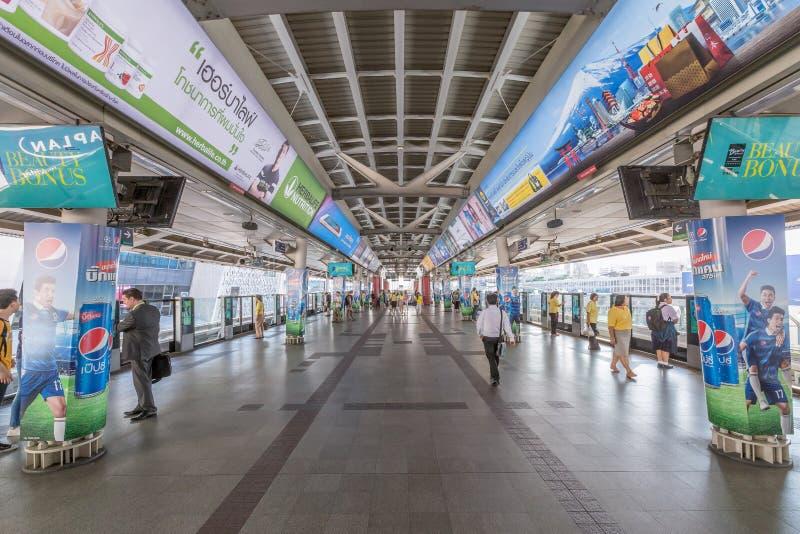 Los pasajeros esperan un tren inminente en una plataforma en una ciudad imagen de archivo