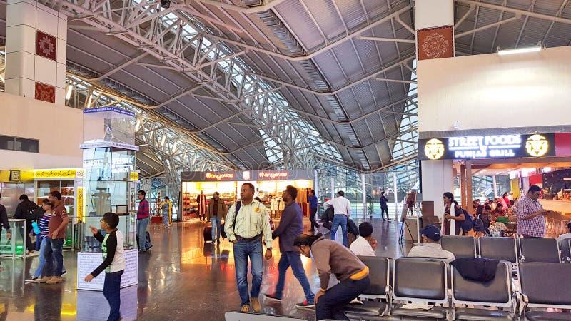 Los pasajeros están esperando su vuelo que se sienta en el salón en el aeropuerto de Indore imagen de archivo libre de regalías