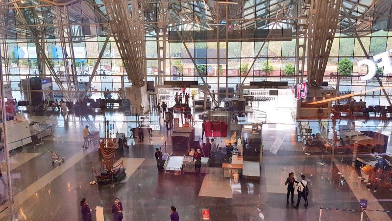 Los pasajeros están esperando su vuelo que se sienta en el salón en el aeropuerto de Indore foto de archivo